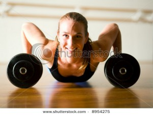 stock-photo-powerful-lady-doing-push-ups-on-dumbbells-8954275